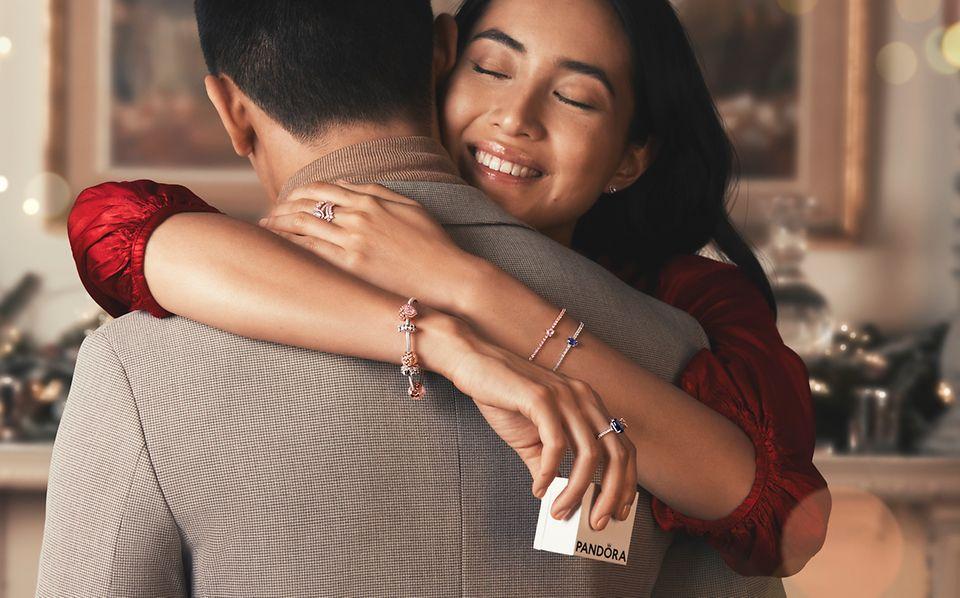Frau mit Pandora Timeless Armband und Ringen umarmt einen Mann