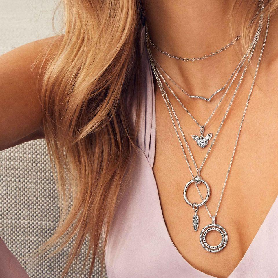 Skapa en personlig look genom lager av olika halsband i sterlingsilver, Pandora Rose och Pandora Shine och trä på berlocker och hängberlocker som förmedlar din stilsaga.