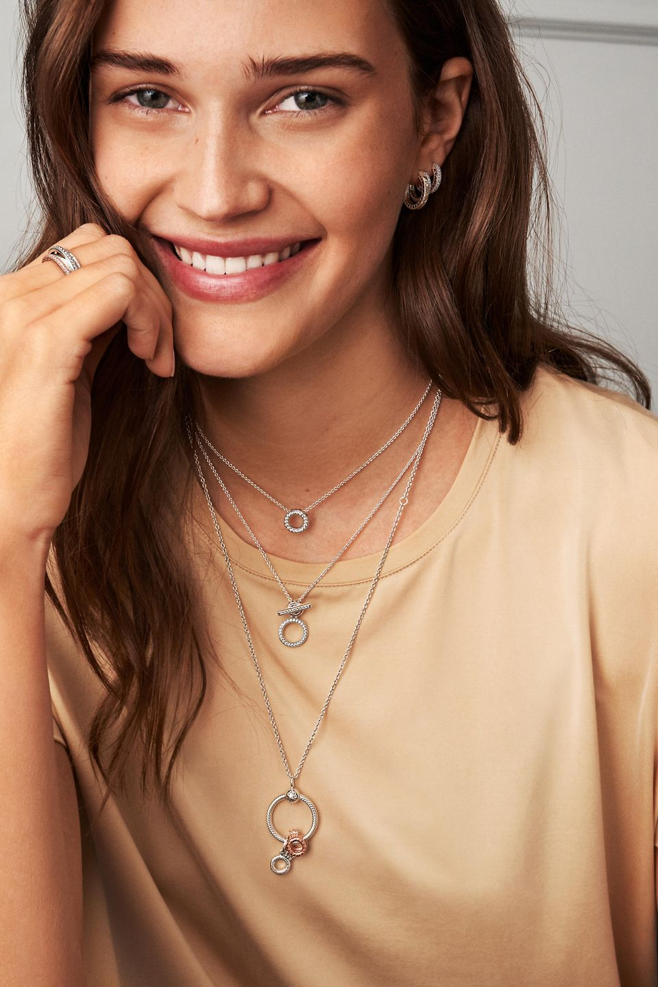 Young woman wearing Pandora Signature collection: necklaces, rings and earrings
