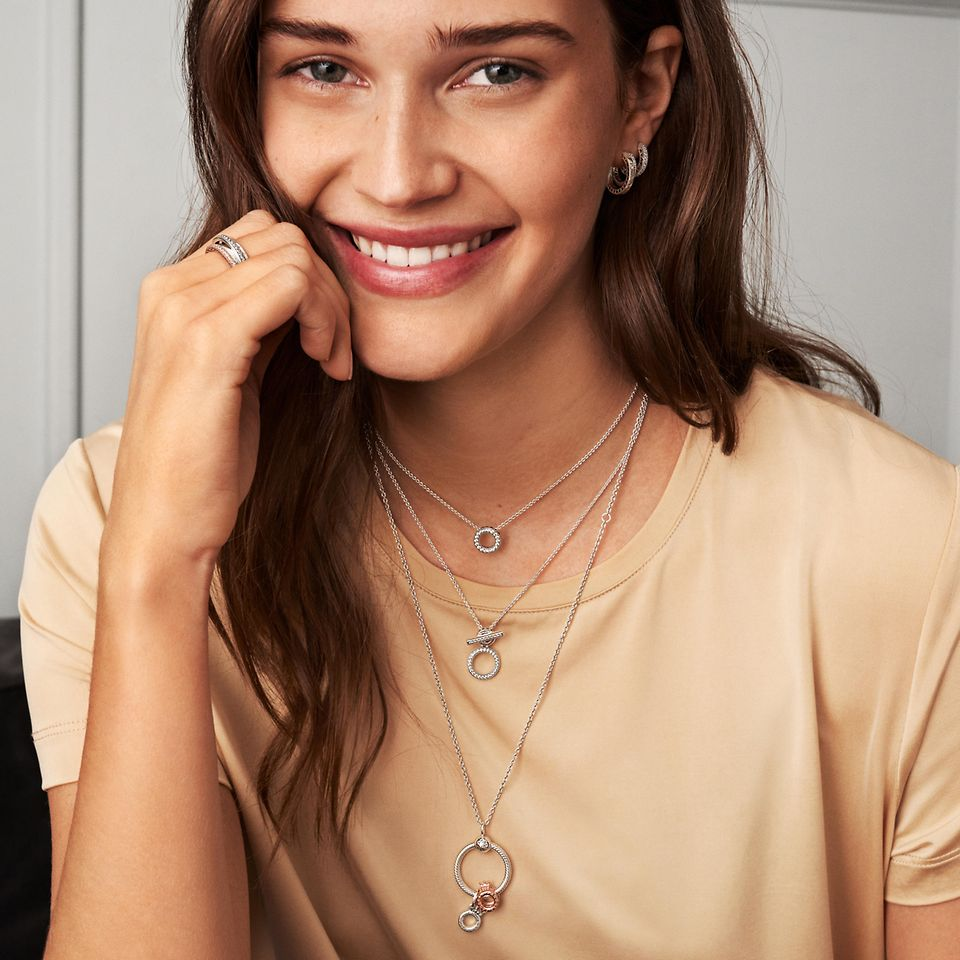Junge Frau mit Pandora Signature Collection: Halsketten, Ringe und Ohrringe