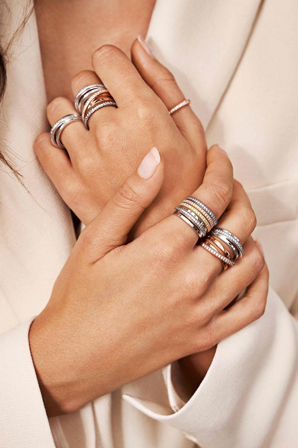 A model's hands wearing Pandora stackable rings in sterling silver and Pandora Rose