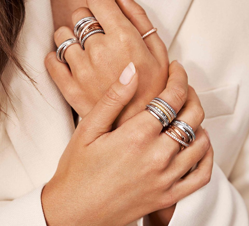 A model's hands wearing Pandora stackable rings in silver and Pandora rose