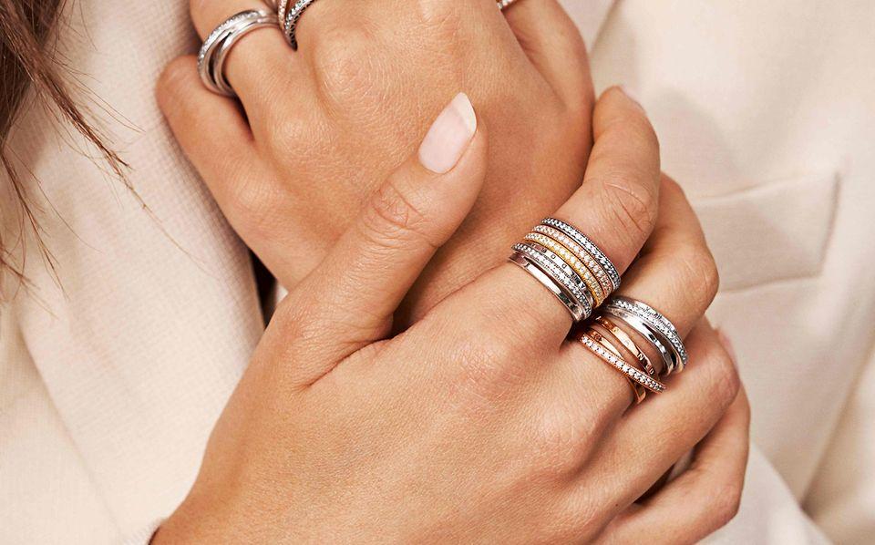 Hand mit Pandora Ring-Stackings aus Silber und Pandora Rose