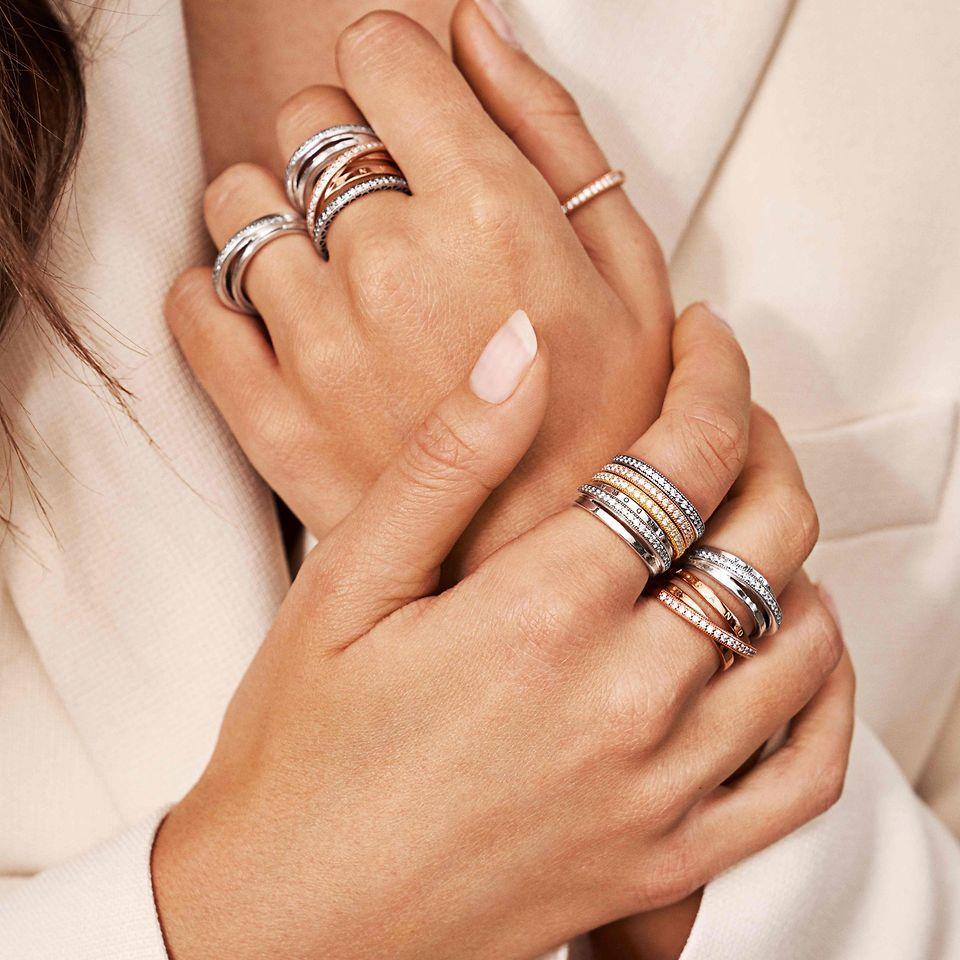 En modells hand som bär Pandoras stapelbara ringar i silver och Pandora Rose