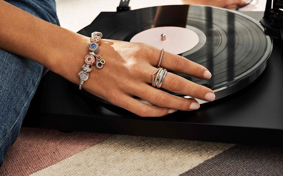 黑膠唱片襯托下,一隻手上佩戴 Pandora Signature 疊戴戒指和串飾手鏈