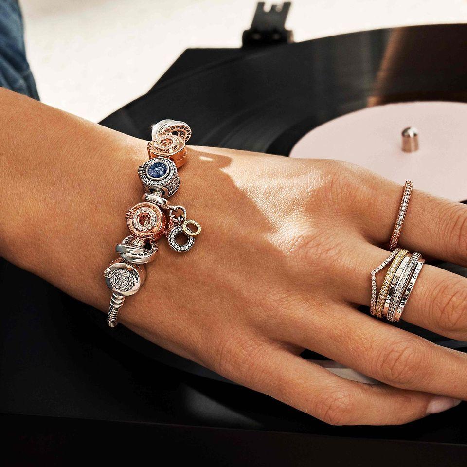 Dłoń na płycie winylowej, ozdobiona zestawami pierścionków i bransoletką modułową Pandora Signature